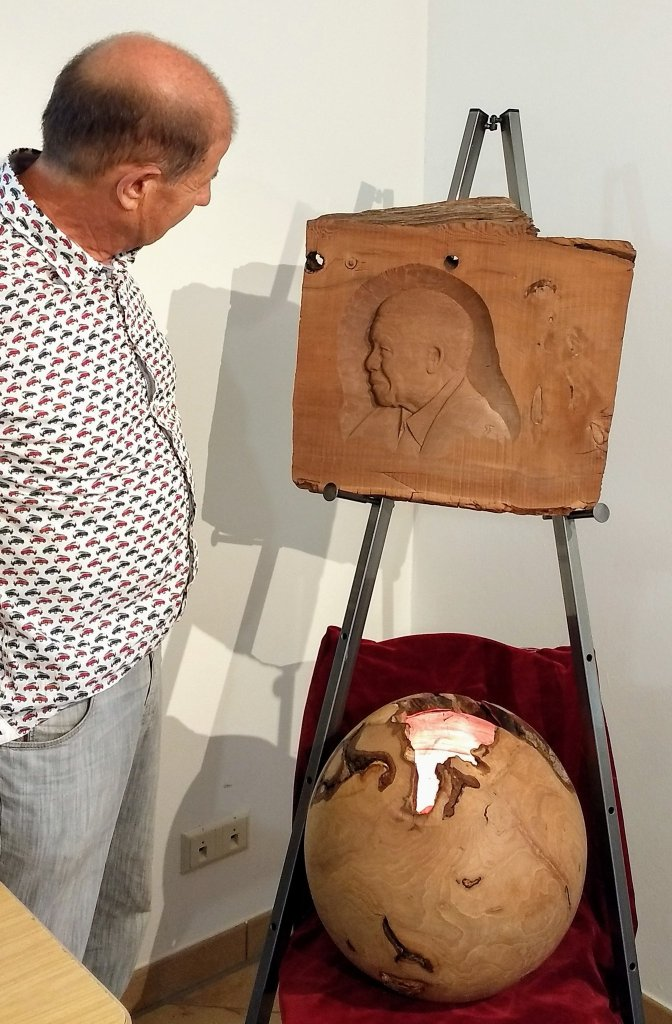 Toni Santa vom Moorlärche Museum aus Südtirol steht im ersten Raum der Moorlärche Ausstellung im Haus der Stadtgeschichte in Hohenmölsen. Er ist im Profil abgebildet und blickt auf das rechts auf einer Staffelei stehende Relief von Nelson Mandela aus braun schimmernden Moorlärche Holz. Mandela ist als ältester Mann abgebildet, seine Büste erscheint im Profil mit Blick nach links. Darunter steht eine Kugel aus Zirbenholz mit Ähnlichkeit zur Erdkugel. Eine Öffnung erinnert an die Umrisse des Kontinents Afrika.