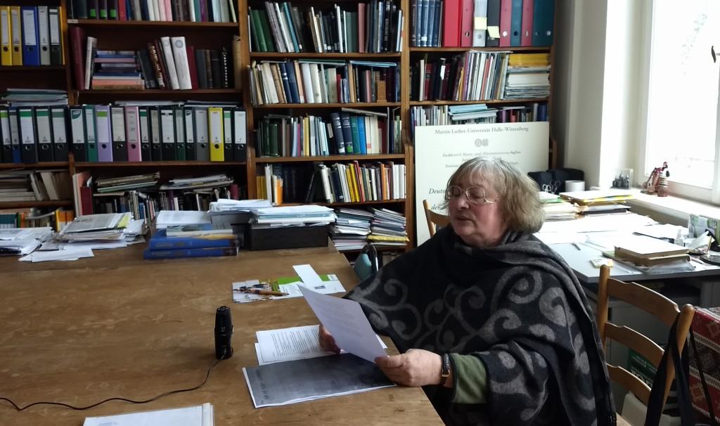 Frau Professor Drost-Abgarjan sitz an einem großen Tisch in ihrem Büro und liest das Gedicht. Sie hat ergraute Haare und ist in ein großes Tuch mit grau-schwarzem Muster gehüllt. Im Hintergrund steht ein großes Bücherregal voller Bücher und Aktenordner.